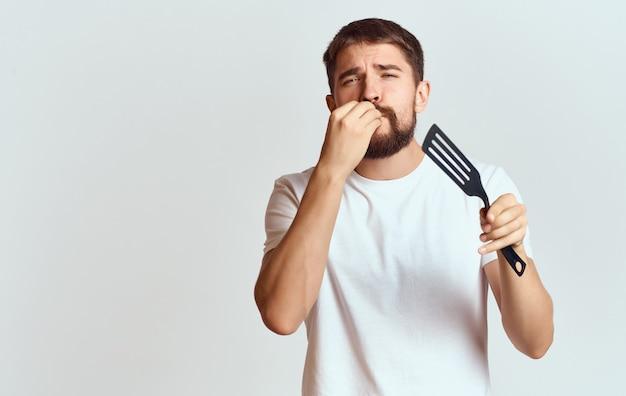 ひげを生やした男の肩甲骨の手は、食品の白いtシャツを準備します。高品質の写真