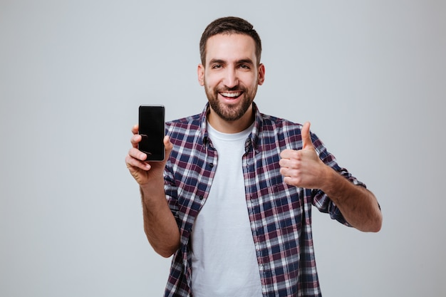 Uomo barbuto che mostra lo schermo e il pollice in bianco dello smartphone su