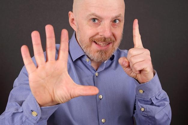 수염 난된 남자 한 손을 위로 및 다른 정지 신호를 보여줍니다.