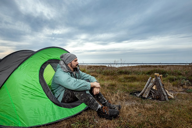 A bearded man sits camping in a tent against the backdrop of nature and the lake.  travel, tourism, camping.