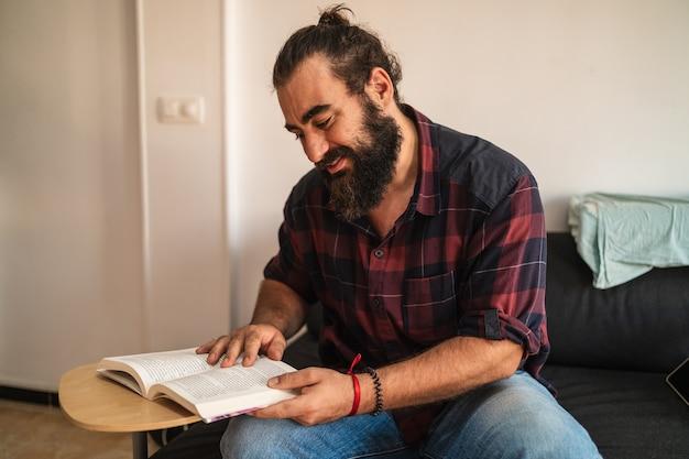 Бородатый мужчина сидит на диване и читает книгу