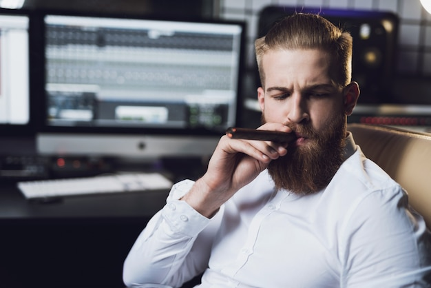 Bearded man sits in studio and smokes cigar.
