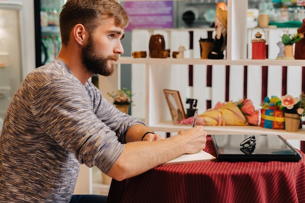 A bearded man sits at a table in a cafe and writes in a notebook