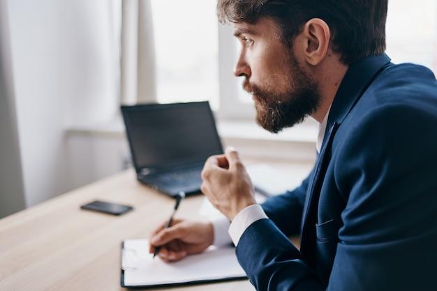 ノートパソコンの金融技術の前の机に座っているひげを生やした男