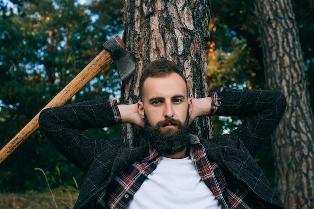 Бородатый мужчина сидит рядом с деревом