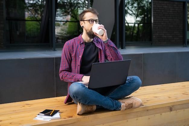 Бородатый мужчина, сидя со скрещенными ногами на деревянной скамейке с ноутбуком