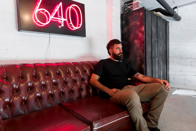 Бородатый мужчина, сидя на диване в парикмахерской