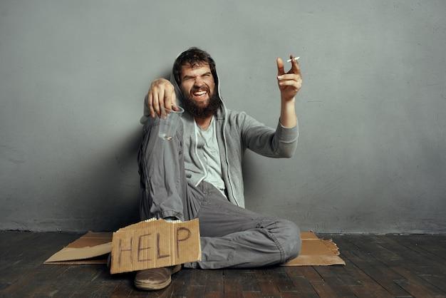 돈 문제 우울증을 구걸 바닥에 앉아 수염 난된 남자