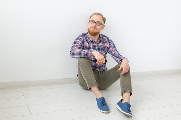 Бородатый мужчина сидит на полу с телефоном, светлая поверхность с копией пространства