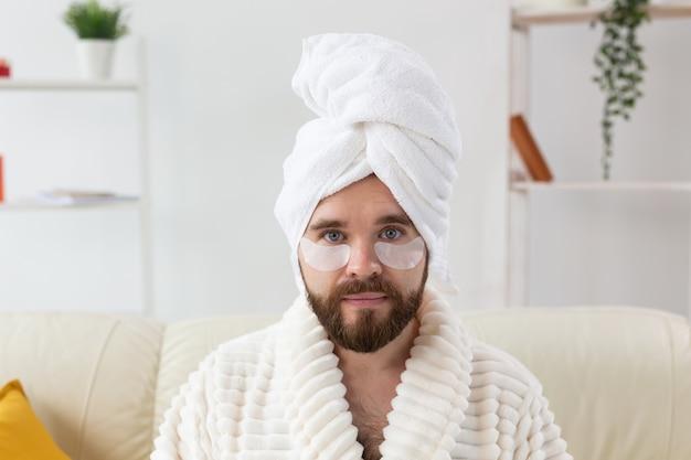 Бородатый мужчина сидит с повязками на глазах. уход за морщинами и лицом в домашних условиях для мужчин.