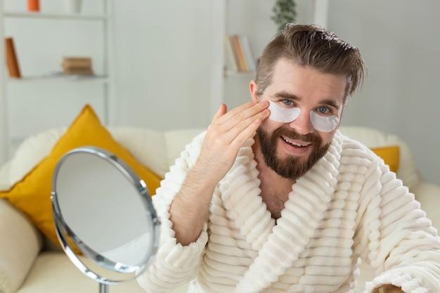 Бородатый мужчина сидит с повязками на глазах, морщины и уход за лицом в домашних условиях для мужчин
