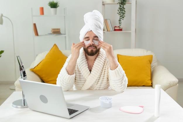 얼굴 주름에 안대를 하고 앉아 있는 수염 난 남자와 남성을 위한 홈 케어