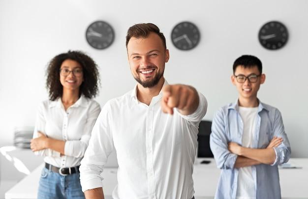 Бородатый мужчина улыбается и указывает на камеру, стоя рядом с уверенными членами международной команды в современном офисе ит-компании