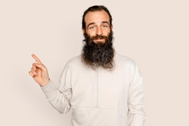 Uomo barbuto che sorride e indica il lato