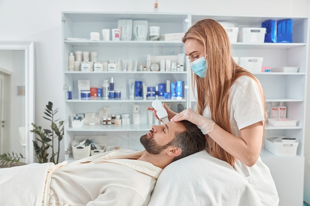 Bearded man smiling in professional beauty spa salon during ultrasonic facial cleansing procedure.
