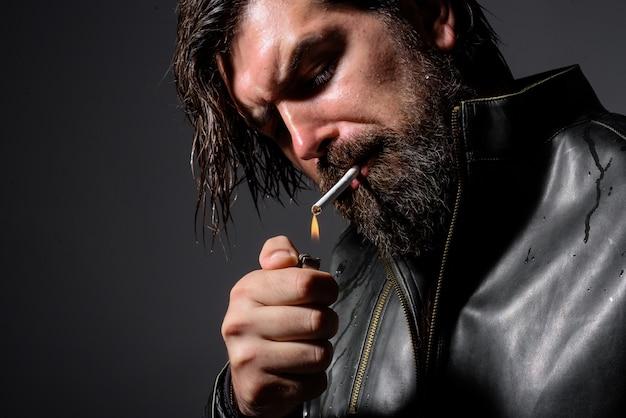 수염 난 남자 라이터와 담배 연기 관능적인 담배 세련 된 힙 스터를 연기