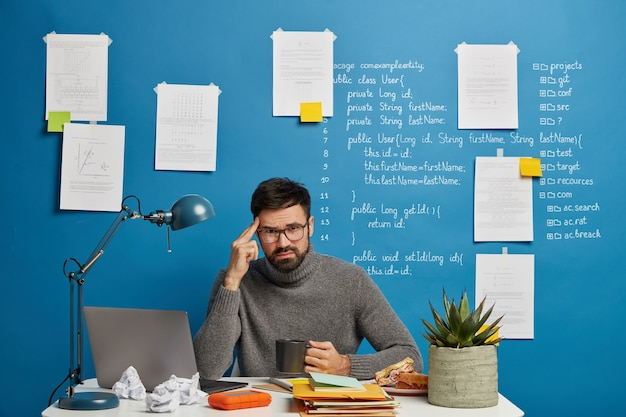 Bearded man in spectacles ponders over startup project, has unhappy expression, tries to concentrate, drinks coffee, does remote job in own cabinet