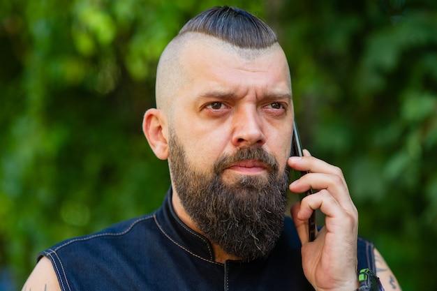 通りに立って携帯電話で話しているひげを生やした男。カジュアルな服装でひげを生やした男の肖像画