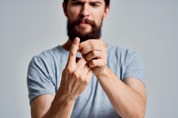 あごひげを生やした男は、健康上の問題を治療する石膏で彼の指を刺します