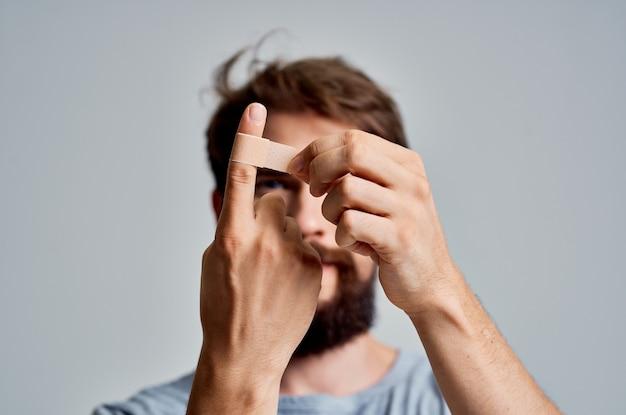수염 난 남자는 건강 문제를 치료하는 석고로 손가락을 찌른다