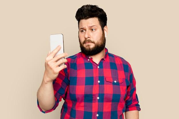 スマートフォンのデジタルデバイスで音楽をストリーミングするひげを生やした男