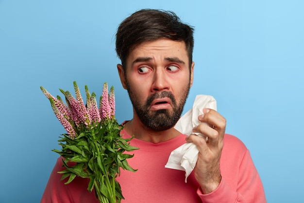 Bearded man suffers from allergic rhinitis, holds napkin and looks unhappily at allergen, feels sick, has runny nose and constant sneezing, needs effective medicines to cure disease