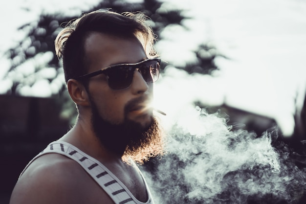 A bearded man in sunglasses smokes a cigarette at sunset, releases a thick tobacco smoke