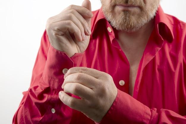 Бородатый мужчина снимает раздеваться красную рубашку