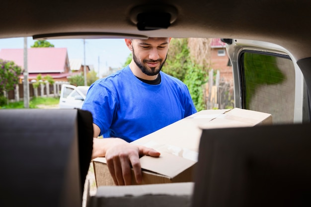 Bearded man taking delivery boxes out of van
