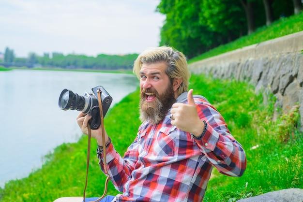 사진을 취미로 찍고 여행하는 수염 난 남자 거리에서 카메라로 사진을 찍는 젊은 남자