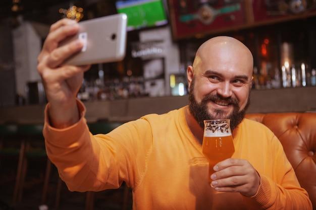 Бородатый мужчина берет селфи со стаканом пива в руке, используя смартфон в пабе