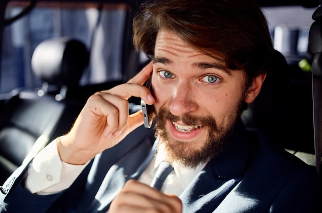 Bearded man talking on the phone in a car trip