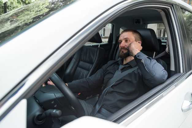 Bearded man talking on the phone while driving