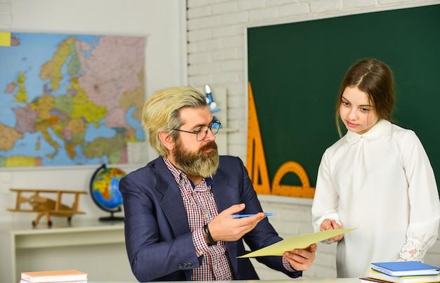 Учитель бородатый мужчина в классе. учитель проверяет правильный ответ. следите за успеваемостью ученика. учебные материалы. кого сегодня нет. концепция обучения. индивидуальное занятие. домашнее обучение. обратно в школу.