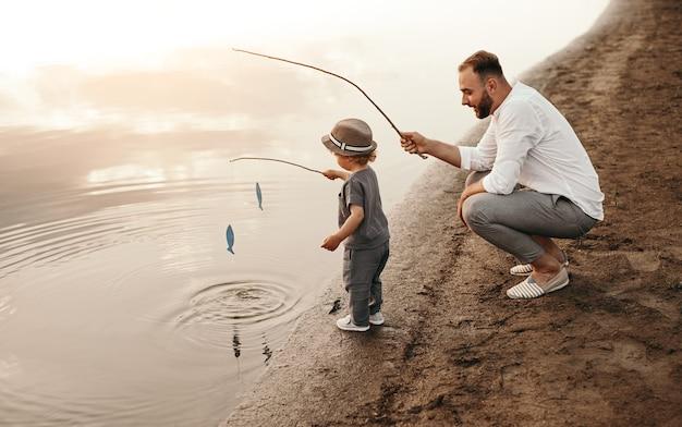 魚を捕まえるために男の子を教えるひげを生やした男