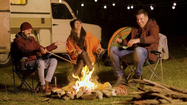 キャンプファイヤーの周りで彼の友人に面白い冗談を言っているひげを生やした男。レトロなキャンピングカー。キャンプのテント。