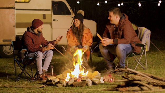 Bearded man telling a funny joke to his friends around camp fire. retro camper van. camping tent.
