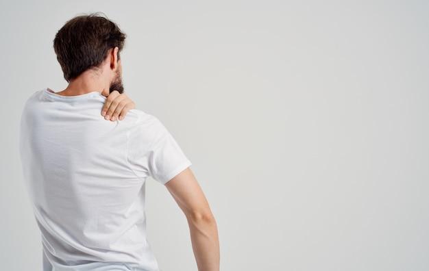 Бородатый мужчина человек в белой футболке страдает от боли