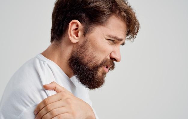 Бородатый мужчина трогает плечо рукой, болит вывих, медицинское вмешательство