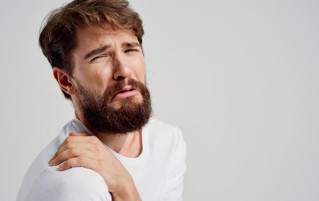Бородатый мужчина трогает плечо с вывихом руки