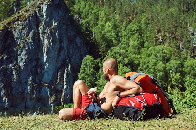山で休んでいるひげを生やした男の観光客。自然を旅しながら休憩とおやつ