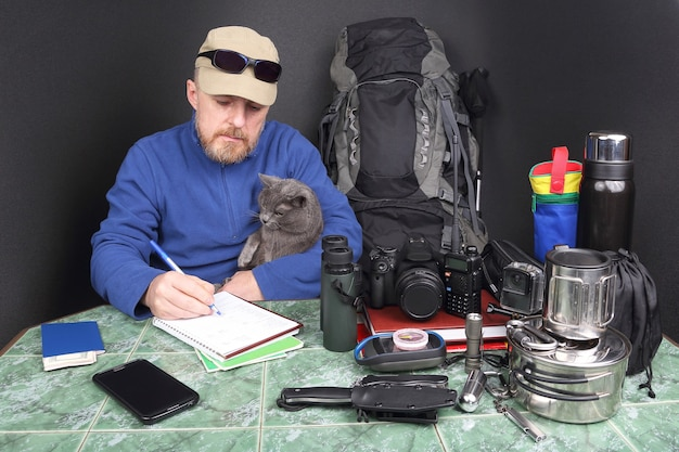Bearded man traveler checks things for a hike in nature