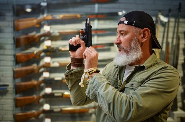 あごひげを生やした男が銃店でピストルボルトをひきつらせます。武器屋のインテリア、弾薬と弾薬の品揃え、銃器の選択、射撃の趣味とライフスタイル、護身術