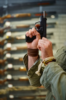 あごひげを生やした男が銃店でピストルボルトをひきつらせる