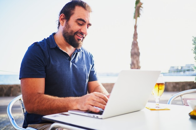 Bearded man using computer in cafeteria terrace and having a beer