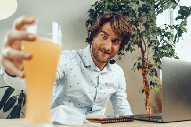 Бородатый мужчина, используя свой ноутбук, выпивая стакан пива