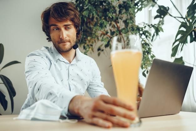 ビールのグラスを飲みながら彼のラップトップを使用してひげを生やした男