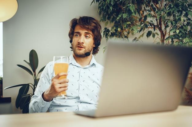 ビールを飲みながらラップトップを使用してひげを生やした男