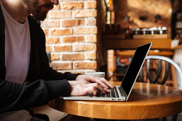 Bearded man using laptop in cafe