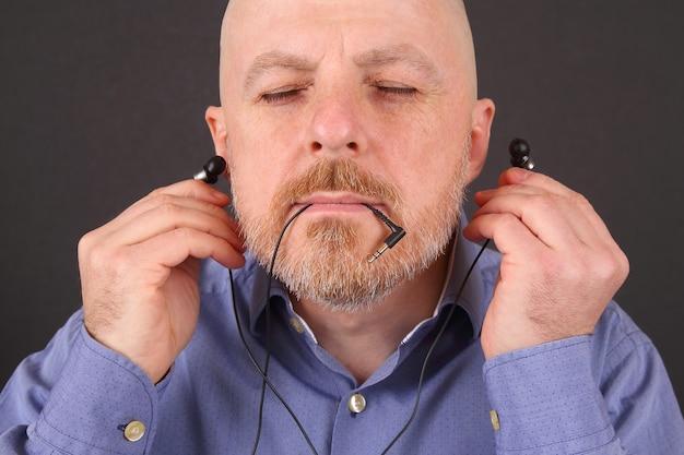 수염 난 남자 진공 헤드폰을 통해 음악을 듣고 싶어
